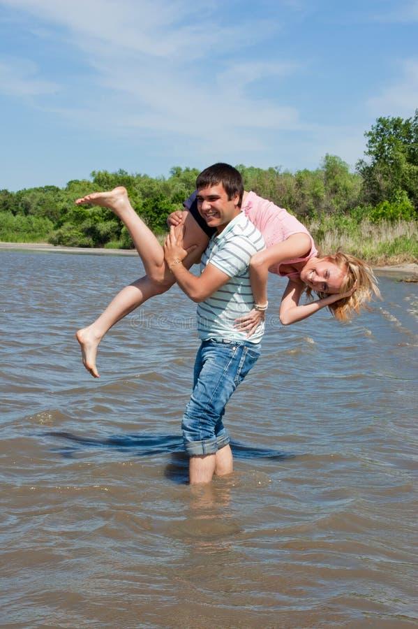 Rapariga e o indivíduo no banco de rio foto de stock