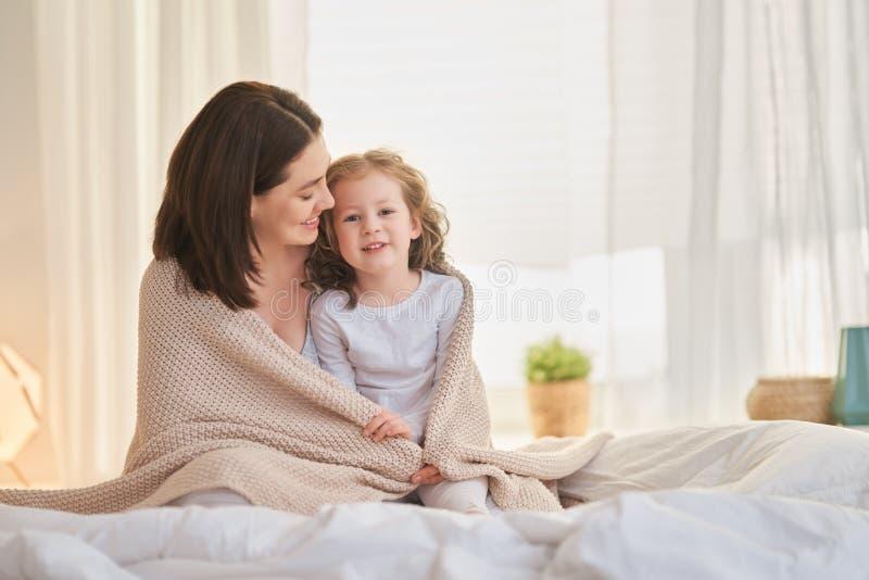 Rapariga e sua mãe gostam de manhã ensolarada fotografia de stock royalty free