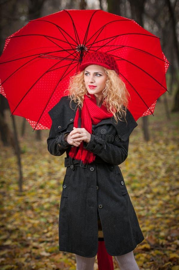 Rapariga elegante bonita com guarda-chuva vermelho, o tampão vermelho e o lenço vermelho no parque
