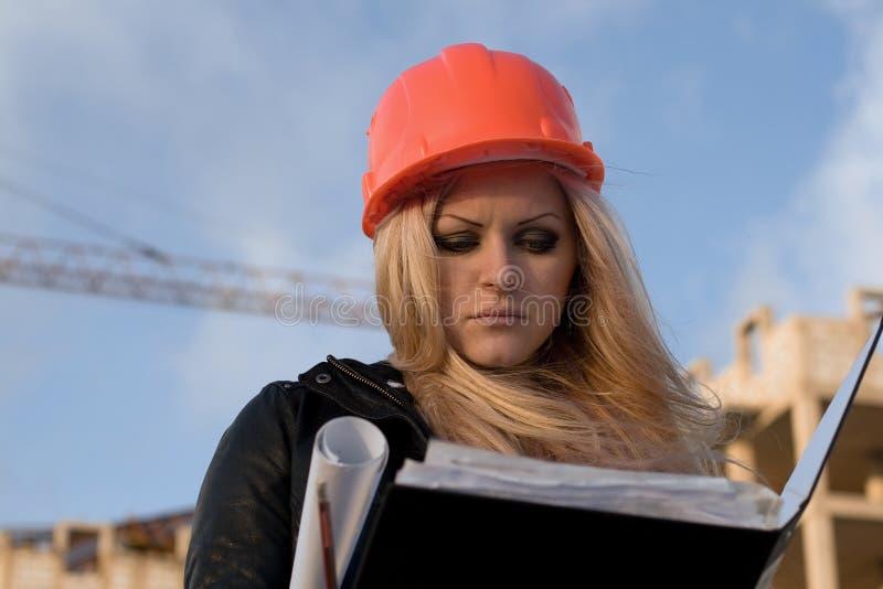 Rapariga em um capacete antes de construir foto de stock