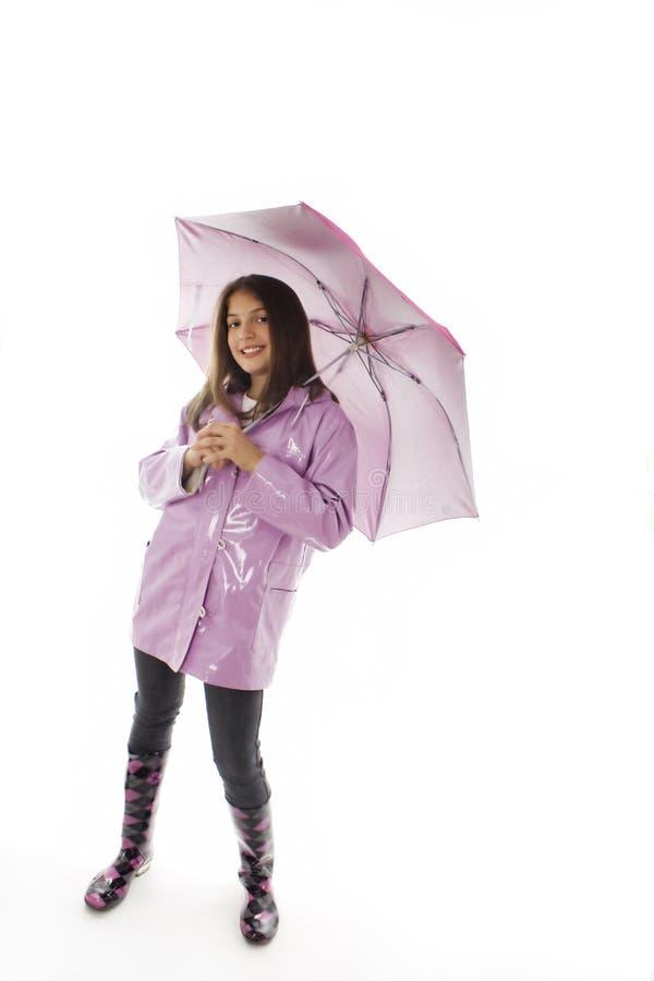 Rapariga em um raincoat e em uma terra arrendada um guarda-chuva imagem de stock