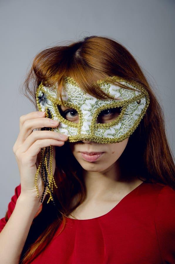 Rapariga em um vestido e em uma máscara vermelhos imagem de stock
