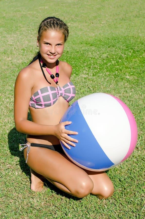 A rapariga em uma grama com uma bola inflável foto de stock royalty free