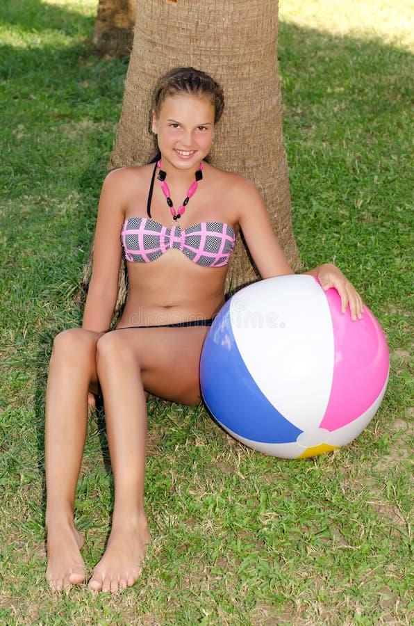 A rapariga em uma grama com uma bola inflável imagens de stock