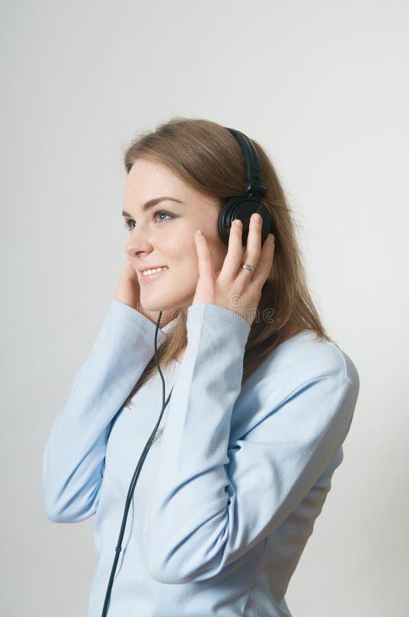 A rapariga escuta a música no auscultadores fotografia de stock royalty free