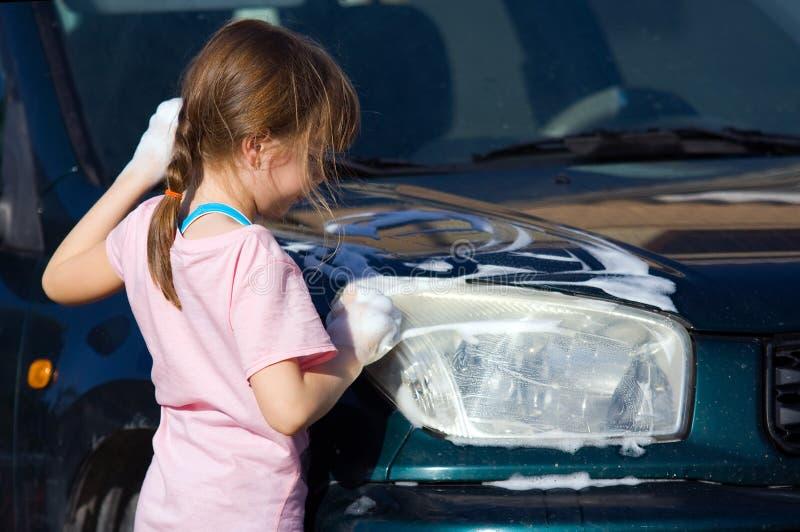 A rapariga esfrega o farol do carro foto de stock royalty free