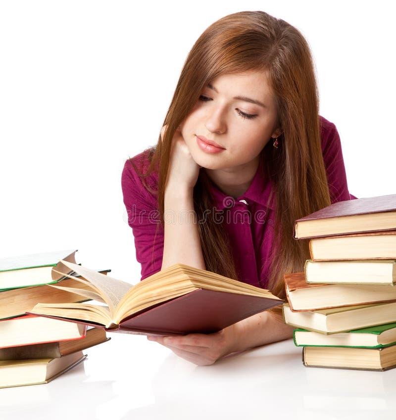 A rapariga está encontrando-se em um livro do assoalho e de leitura foto de stock