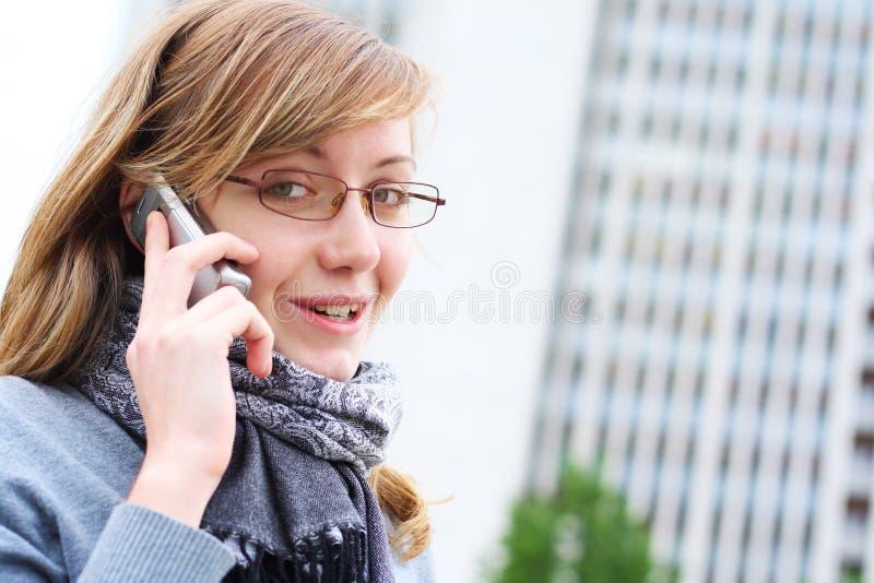 A rapariga fala pelo telefone móvel. Negócio fotografia de stock