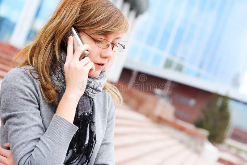 A rapariga fala pelo telefone móvel. Negócio imagens de stock royalty free