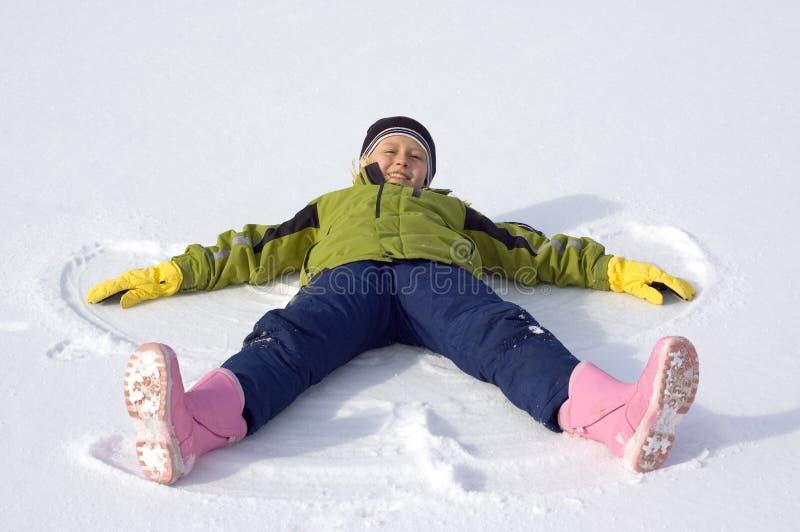 A rapariga faz um anjo da neve imagem de stock royalty free