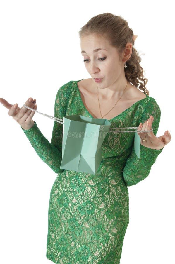 A rapariga feliz bonita olha em um saco do presente da compra. imagem de stock