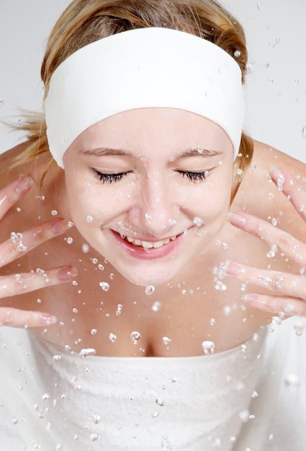 A rapariga feliz lava sua face imagens de stock