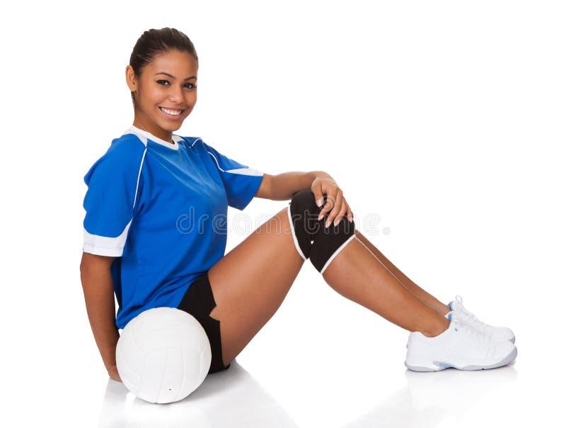Rapariga feliz que senta-se com voleibol imagem de stock royalty free