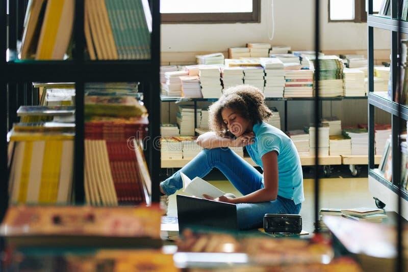 Rapariga Lendo Livro Na Biblioteca foto de stock