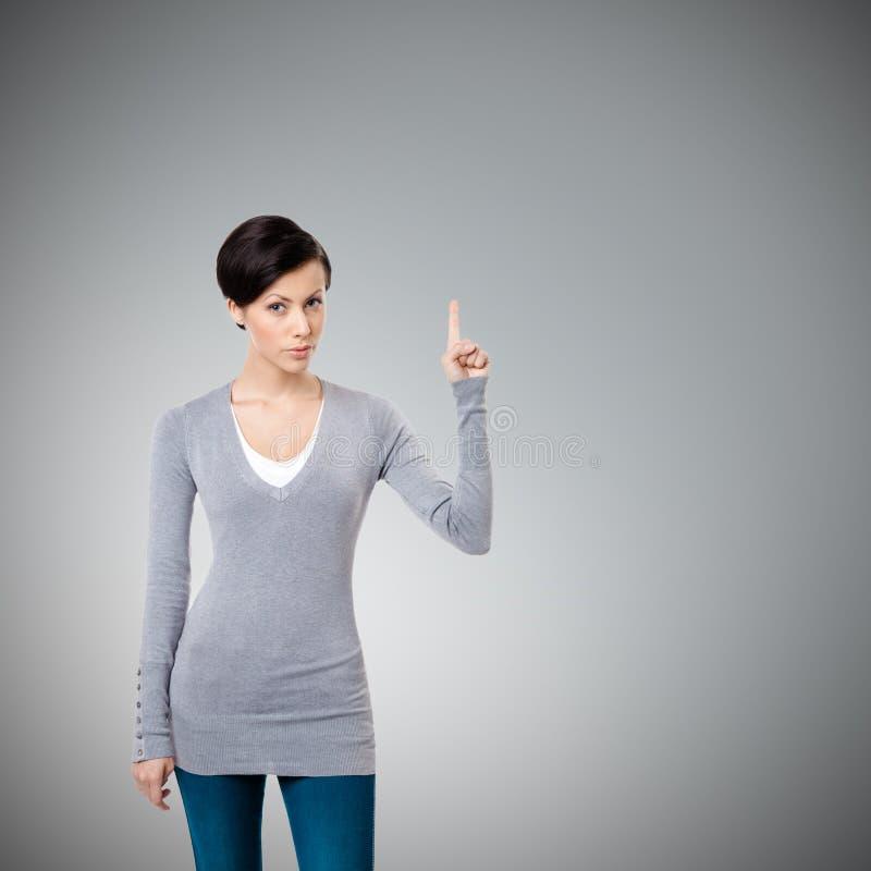 A rapariga mostra o forefinger, sinal da atenção imagens de stock