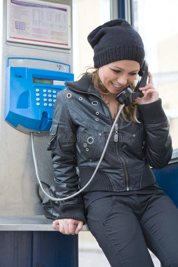 A rapariga na cabine de telefone imagem de stock royalty free