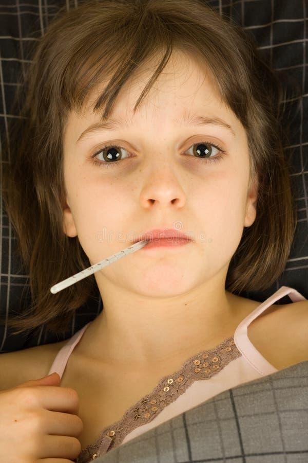Rapariga na cama com febre imagens de stock royalty free