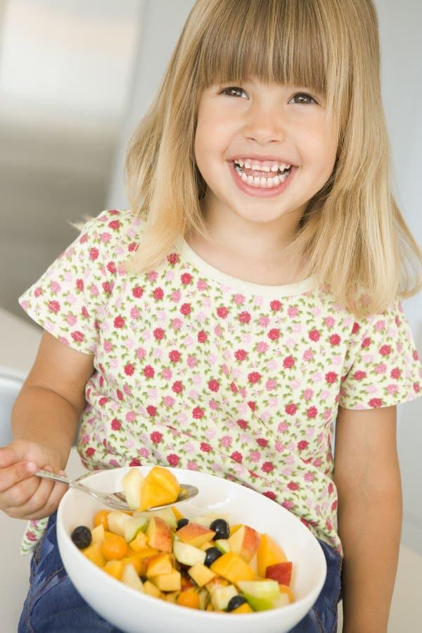 Rapariga na cozinha que come a bacia de sorriso da fruta imagem de stock