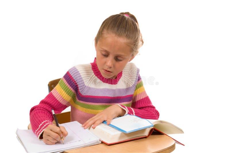 Rapariga na mesa na escola no branco fotos de stock