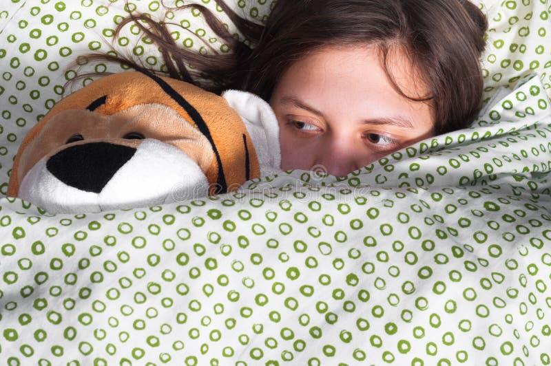 Rapariga na peluche da terra arrendada da cama fotos de stock royalty free