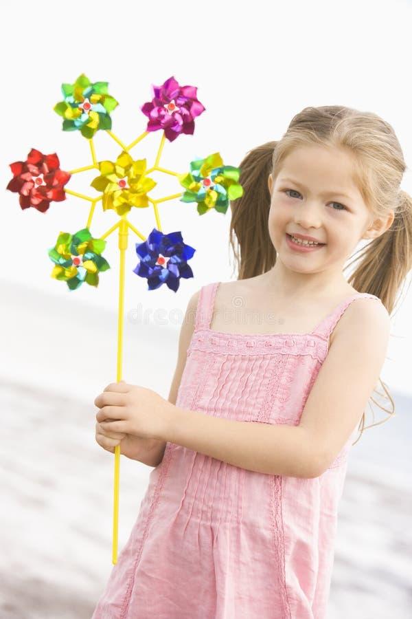 Rapariga na praia com sorriso do moinho de vento do brinquedo fotos de stock