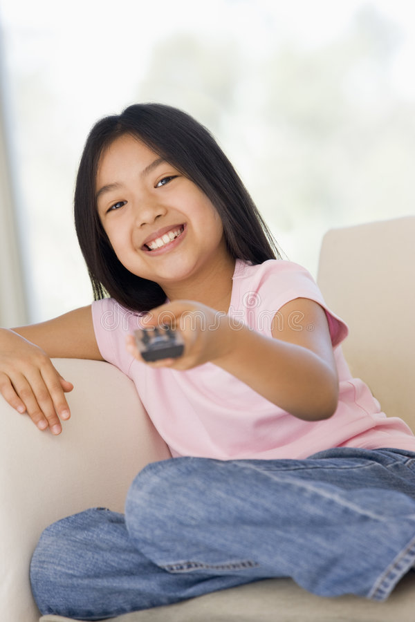 Rapariga na sala de visitas com de controle remoto fotos de stock royalty free