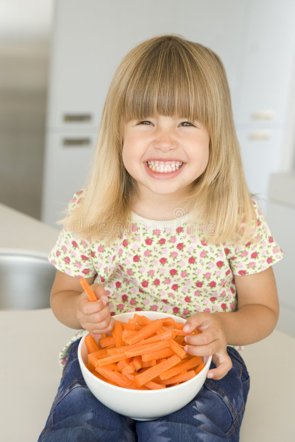 Rapariga no sorriso das varas de cenoura comer da cozinha imagem de stock royalty free