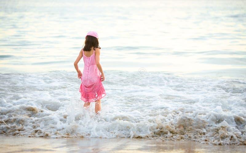 Rapariga no vestido cor-de-rosa que aprecia as ondas imagens de stock royalty free