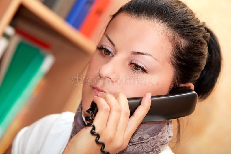 Rapariga os atendimentos da secretária pelo telefone fotografia de stock