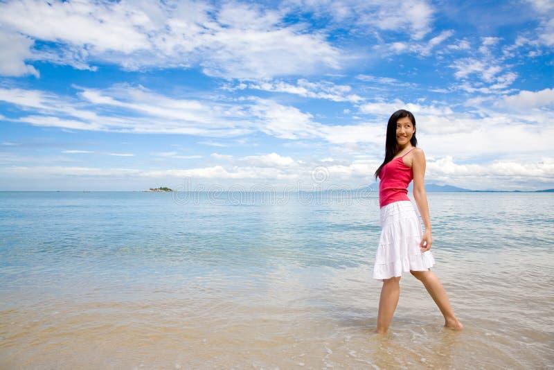 A rapariga pela praia gira para trás o olhar imagem de stock royalty free