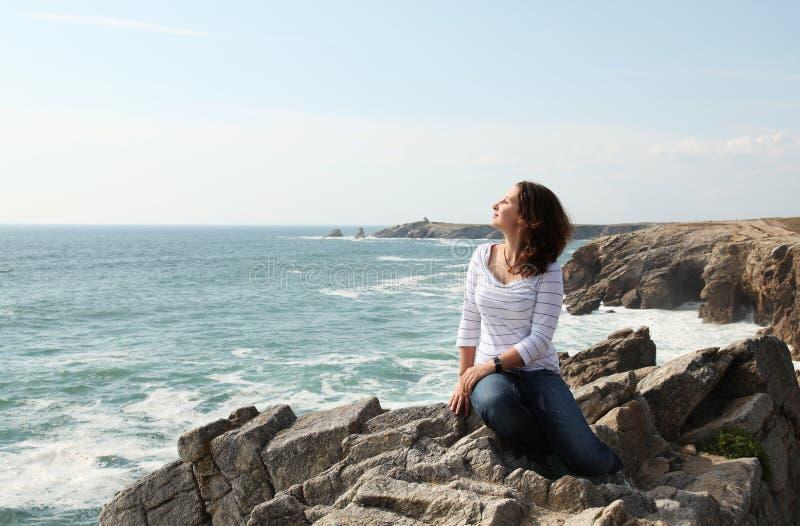 Rapariga que aprecia o vento e o oceano foto de stock royalty free