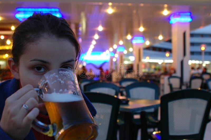 Rapariga que bebe uma cerveja fotografia de stock royalty free