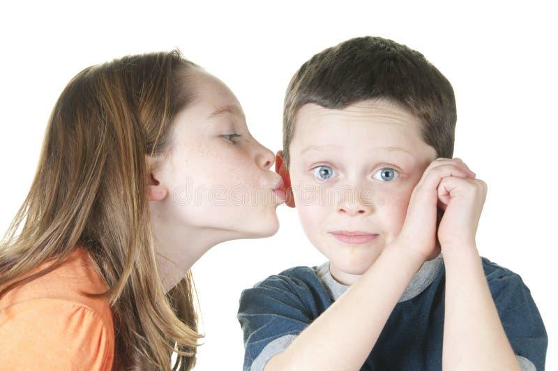 Rapariga que beija o menino no mordente imagem de stock royalty free
