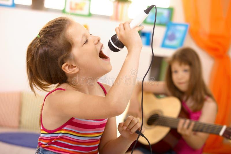 Rapariga que canta com microfone em casa foto de stock royalty free