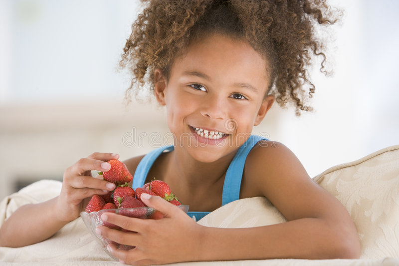 Rapariga que come morangos na sala de visitas fotografia de stock royalty free