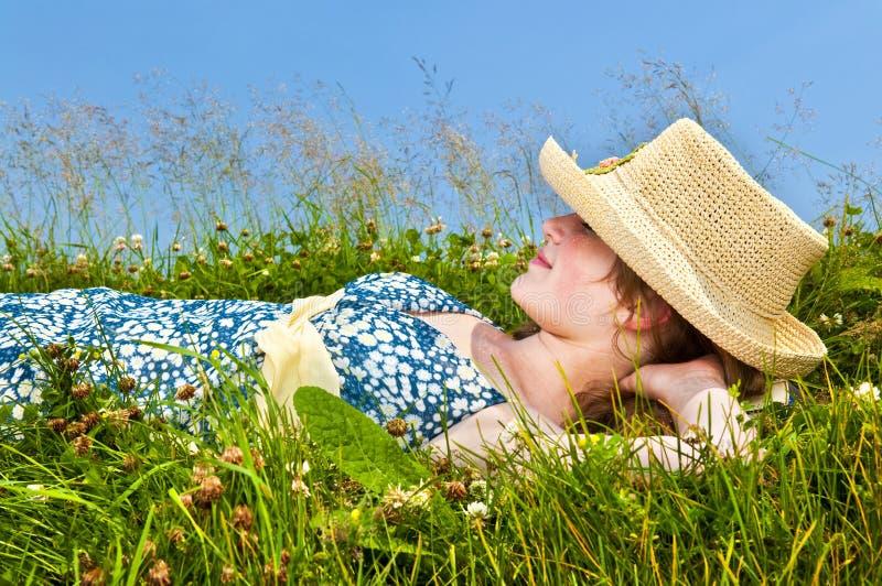 Rapariga que descansa no prado fotos de stock