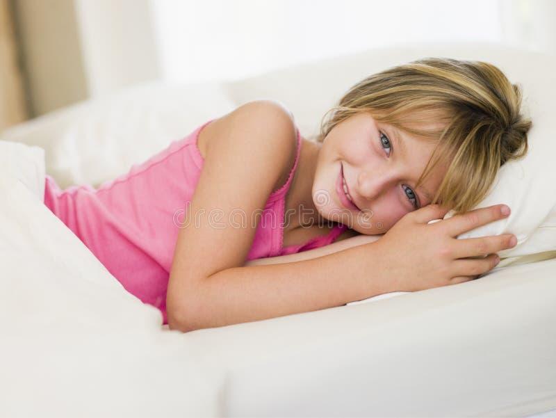Rapariga que encontra-se em sua cama fotografia de stock
