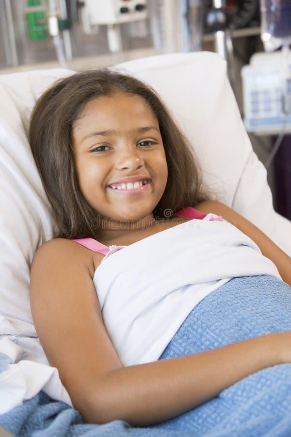 Rapariga que encontra-se na cama de hospital imagem de stock