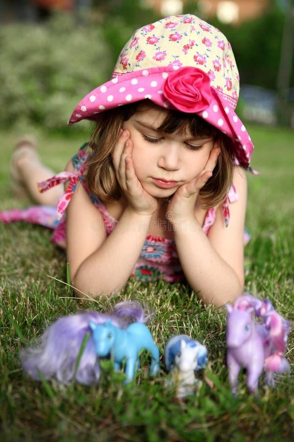 Rapariga que encontra-se na grama, prendendo principal nas mãos fotografia de stock