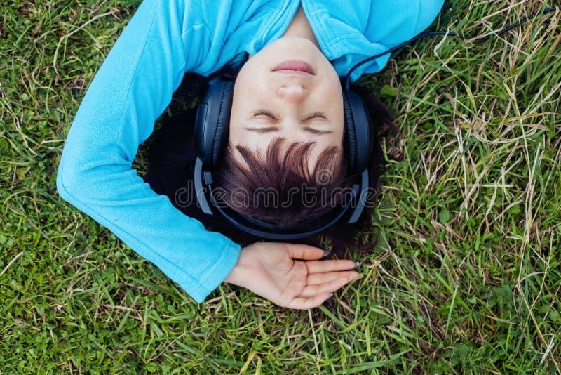 Rapariga que escuta a música em auscultadores Vista superior O conce foto de stock royalty free