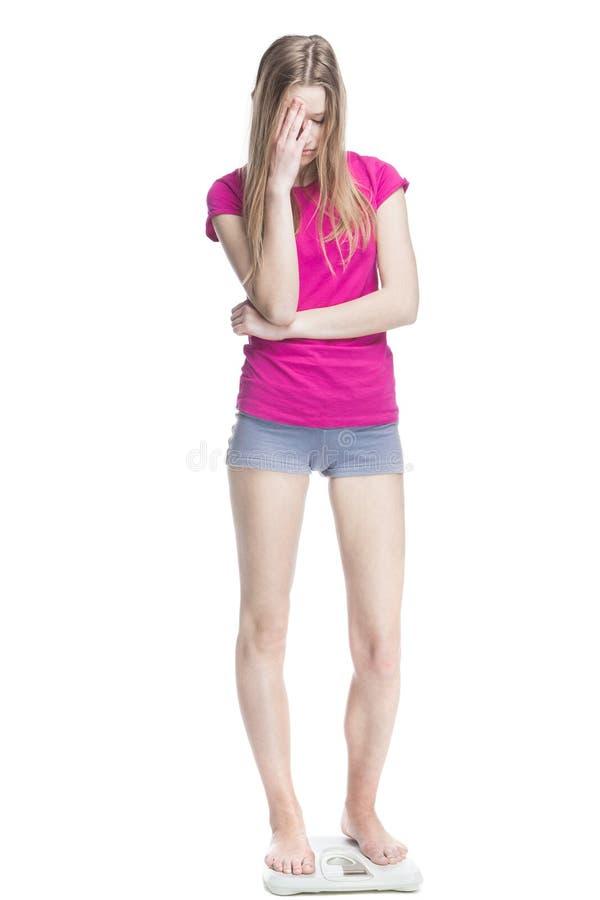 Rapariga que está nas escalas que medem o peso fotografia de stock