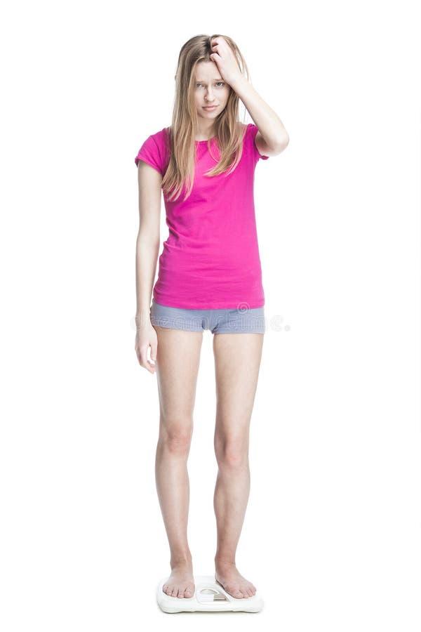 Rapariga que está nas escalas que medem o peso imagens de stock
