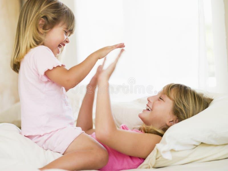 Rapariga que está sendo acordada por sua irmã pequena imagem de stock