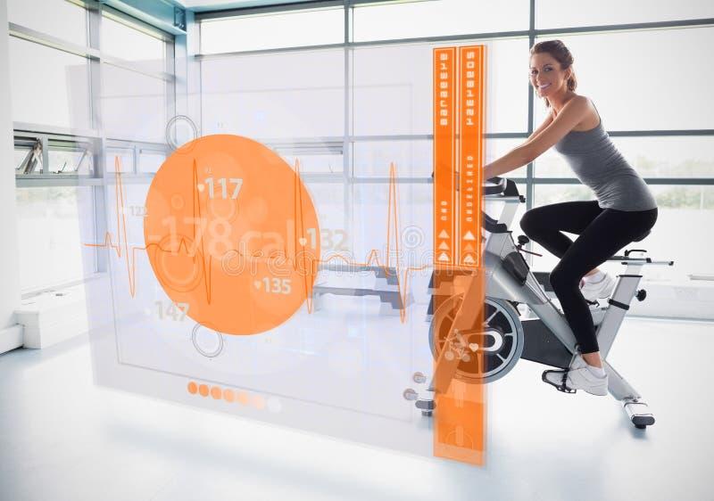 Rapariga que faz a bicicleta de exercício com a relação futurista que mostra calorias fotografia de stock royalty free