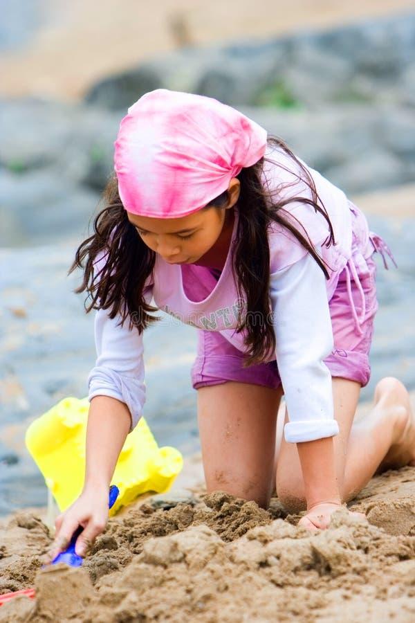 Rapariga que faz o sandcastle fotografia de stock