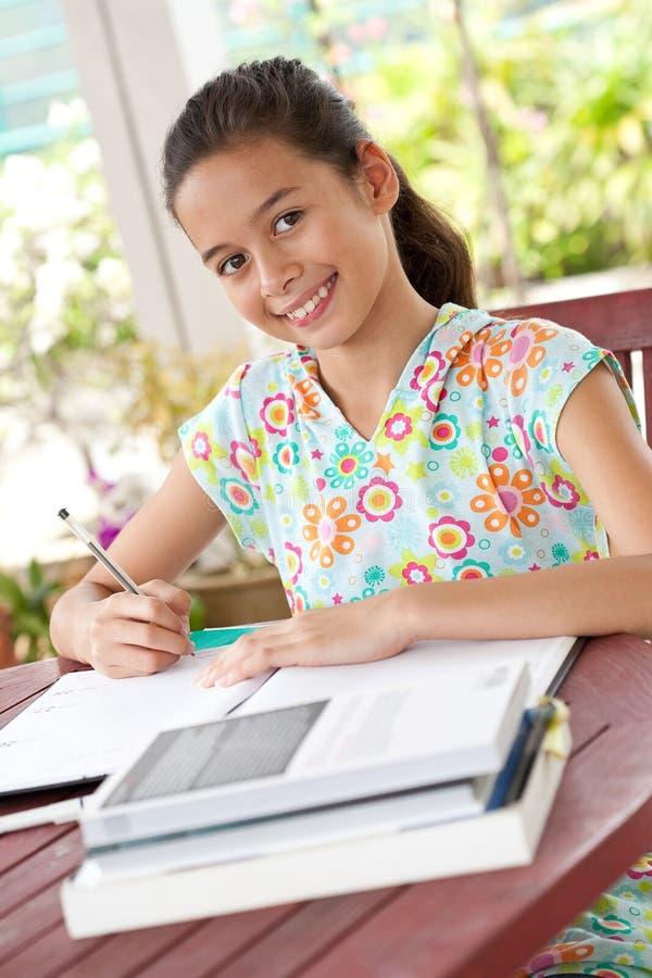 Rapariga que faz seus trabalhos de casa em um ambiente familiar fotos de stock