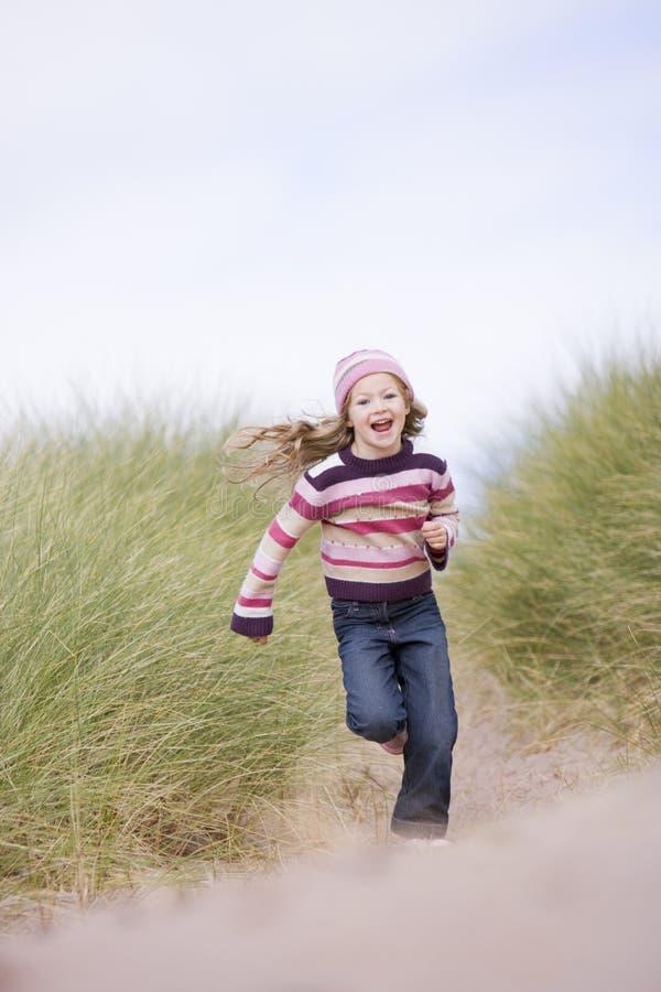 Rapariga que funciona no sorriso da praia fotografia de stock royalty free