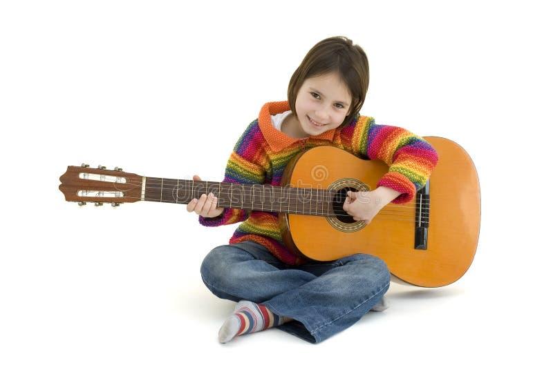 Rapariga que joga a guitarra acústica imagens de stock royalty free