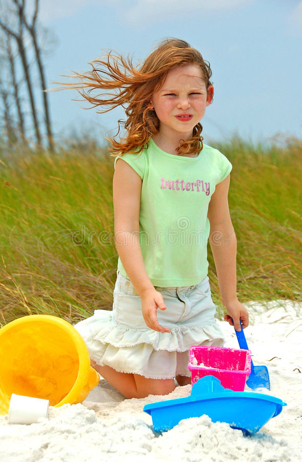 Rapariga que joga na areia da praia fotos de stock royalty free