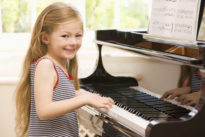 Rapariga que joga o piano fotografia de stock